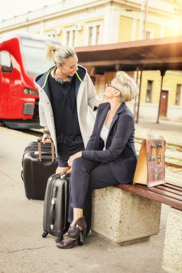 Mujer elegante dos con la reunión de la maleta sobre el ferrocarril imagenes de archivo