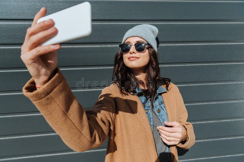 Mujer elegante en el equipo y las lentes de sol negros del otoño que toman el selfie foto de archivo libre de regalías