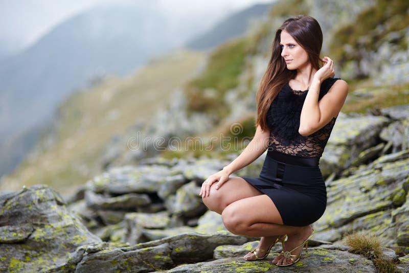 Mujer elegante en el vestido que se sienta en las rocas foto de archivo