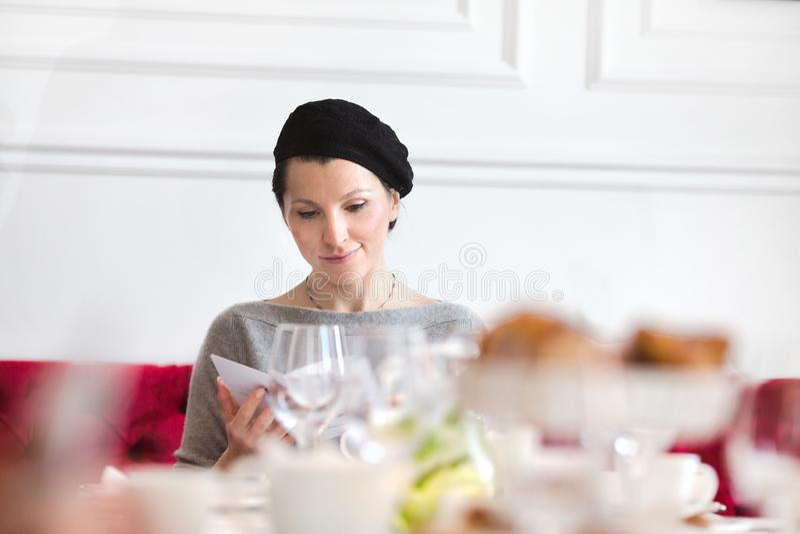 Mujer elegante en la tabla en pasillo del banquete imagen de archivo libre de regalías