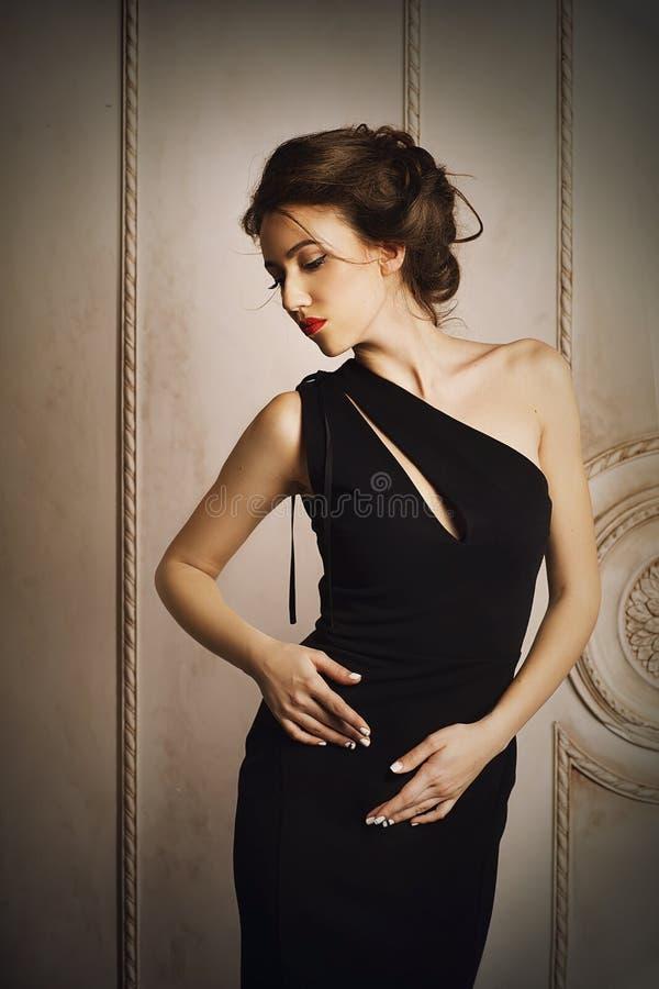 Mujer elegante en vestido negro con el peinado hermoso fotografía de archivo