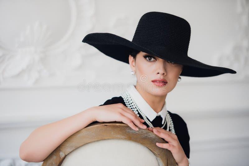 Mujer elegante en vestido negro con un sombrero que se sienta en silla fotografía de archivo
