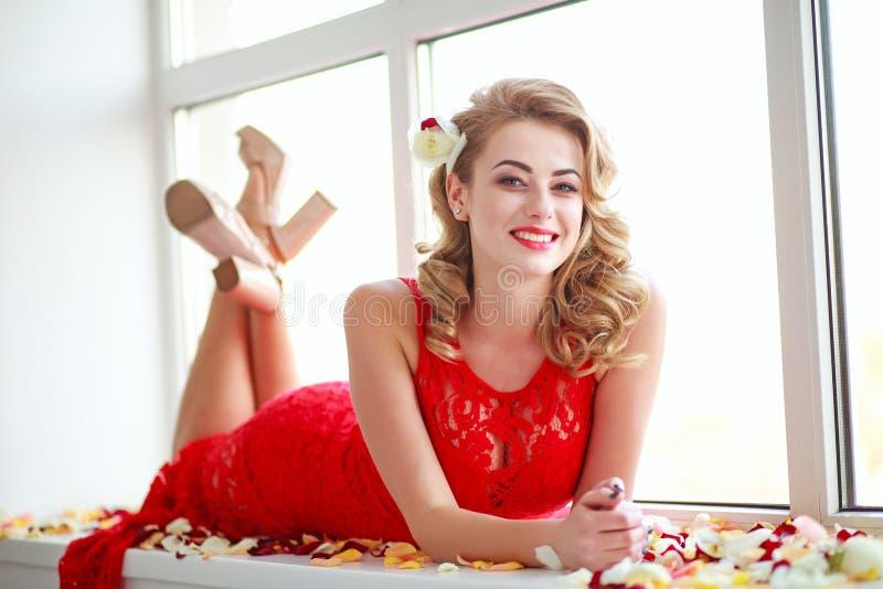 Mujer elegante feliz en vestido en pétalos color de rosa foto de archivo libre de regalías