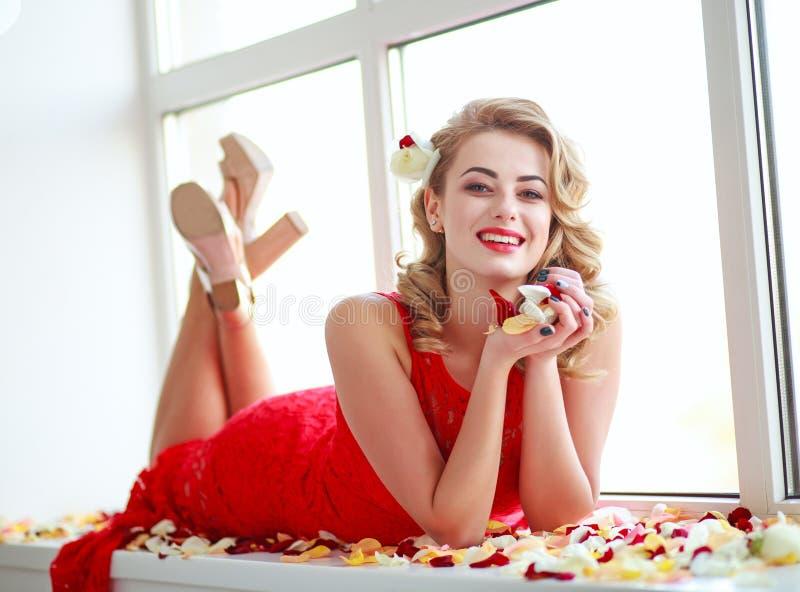 Mujer elegante feliz en vestido en pétalos color de rosa imágenes de archivo libres de regalías