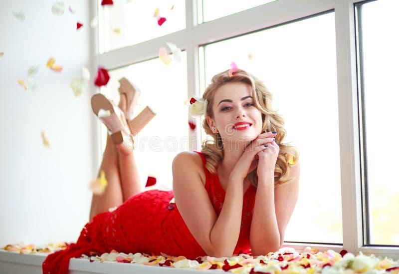 Mujer elegante feliz en vestido en pétalos color de rosa foto de archivo