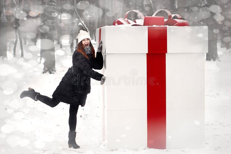 Mujer elegante feliz que sostiene la actual caja grande con la cinta roja con imagenes de archivo