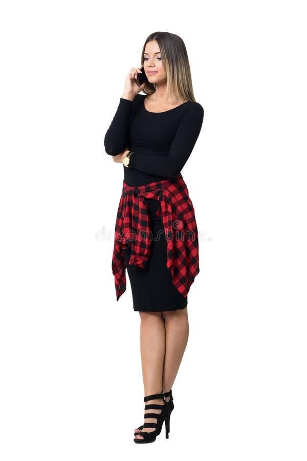 Mujer elegante femenina joven agraciada en tacones altos que habla en el teléfono móvil que mira abajo foto de archivo libre de regalías
