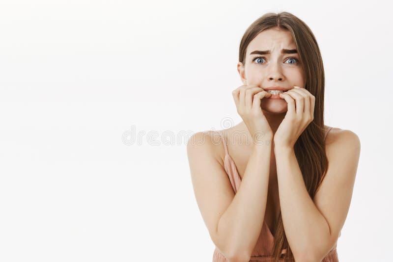 Mujer elegante femenina tímida e insegura asustada con mirar fijamente penetrante de los fingeres del pelo marrón asustado y asus foto de archivo libre de regalías