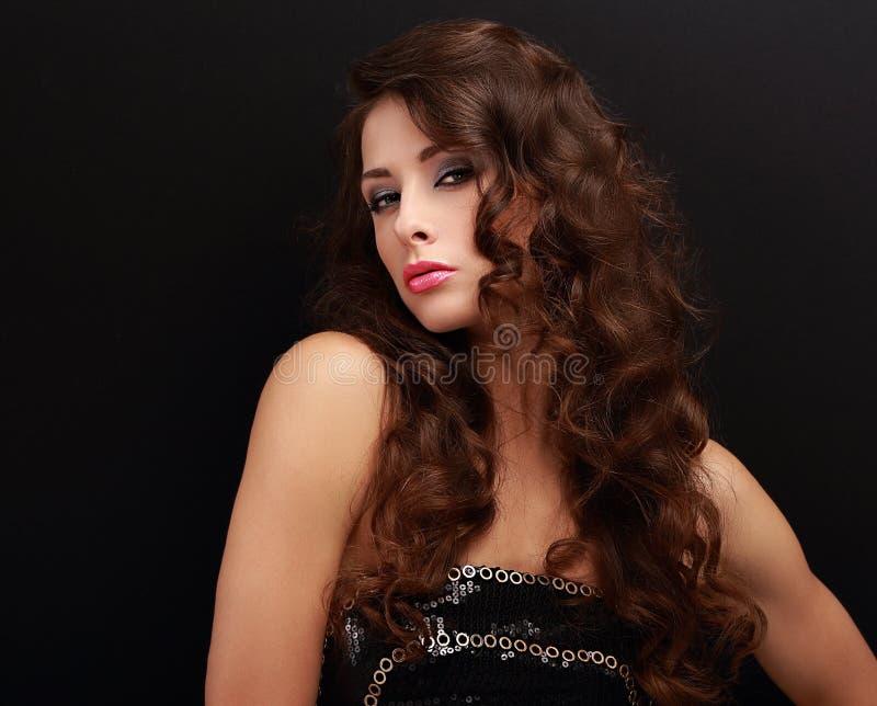 Mujer elegante hermosa con la mirada del estilo de pelo rizado foto de archivo libre de regalías