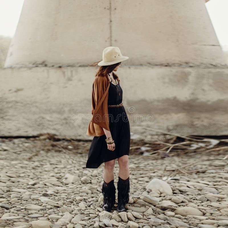 Mujer elegante hermosa del boho con el sombrero, el poncho de la franja y las botas imagen de archivo libre de regalías