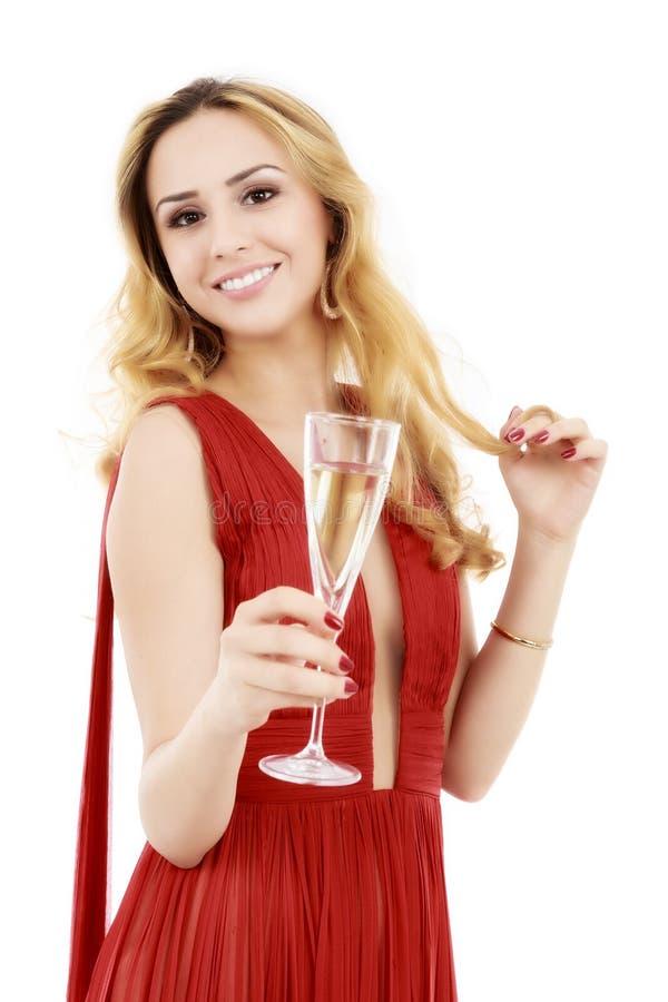 Mujer elegante hermosa en vestido rojo con un vidrio del champán c imagen de archivo