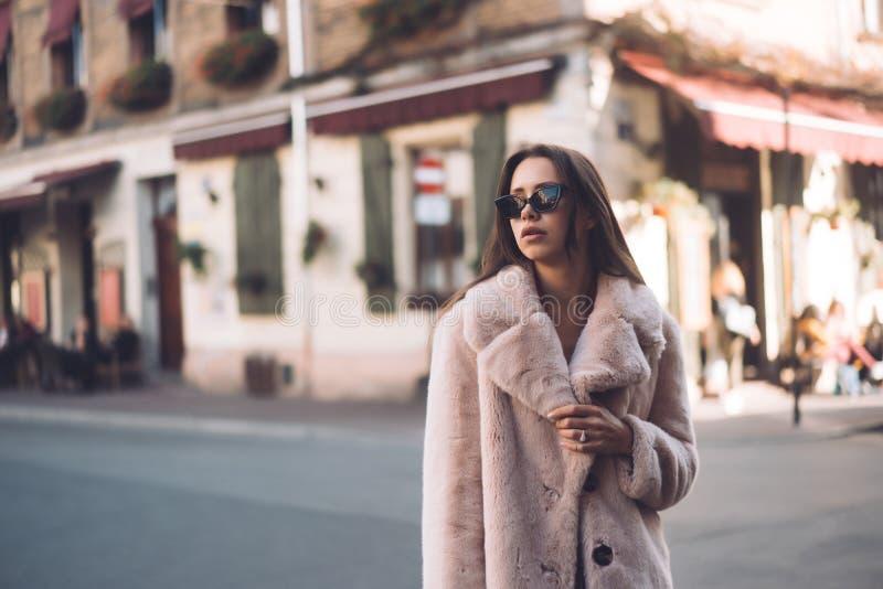 Mujer elegante hermosa joven que camina en capa rosada fotos de archivo libres de regalías
