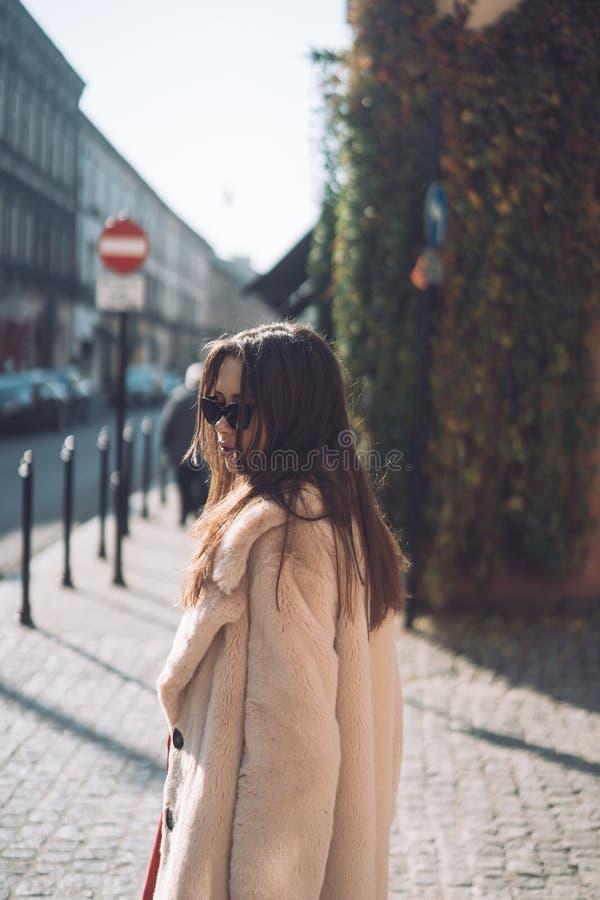 Mujer elegante hermosa joven que camina en capa rosada fotos de archivo