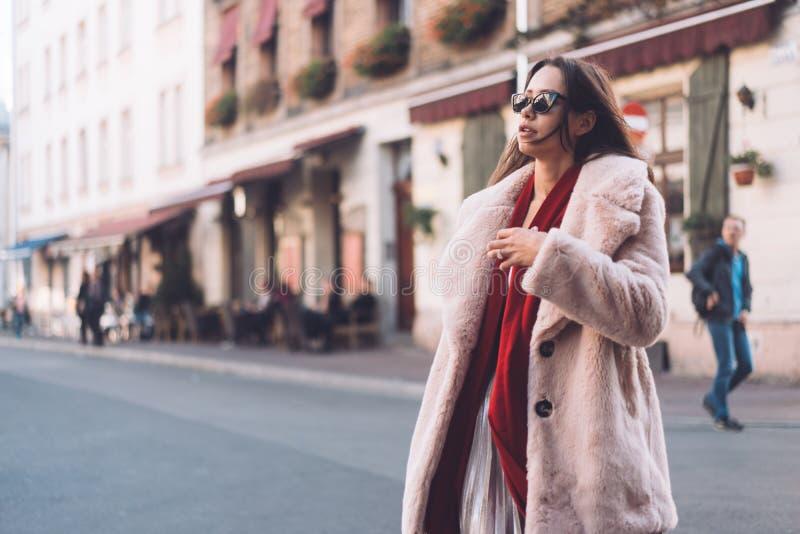 Mujer elegante hermosa joven que camina en capa rosada imagen de archivo