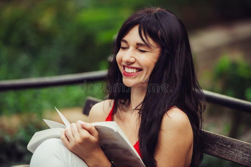 Mujer elegante hermosa que lee un libro y que ríe en el parque verde al aire libre imagenes de archivo
