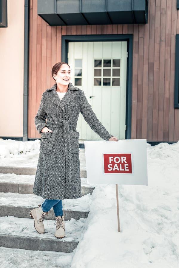 Mujer elegante hermosa que pone en venta la muestra cerca de su casa fotos de archivo libres de regalías