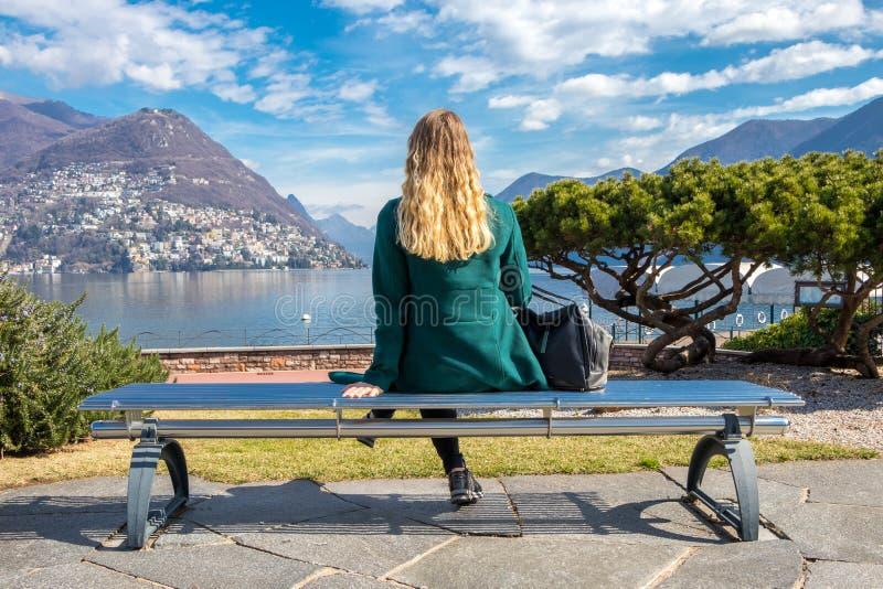 Mujer elegante hermosa que se sienta en un banco de parque y que mira el lago Lugano y montañas de las montañas en el cantón de T fotos de archivo