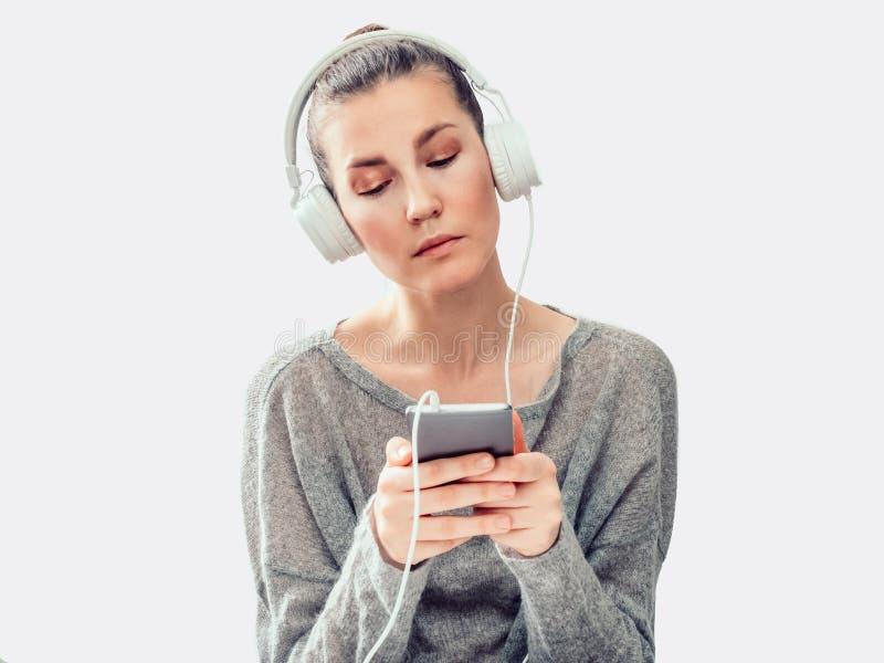 Mujer elegante, joven, auriculares y teléfono móvil imagenes de archivo