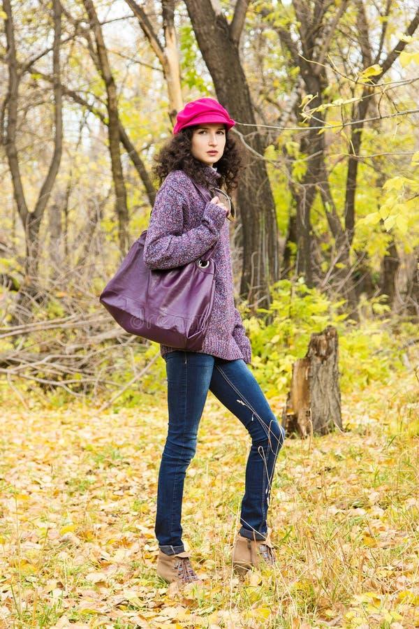 Mujer elegante joven con un bolso grande en el parque del otoño foto de archivo