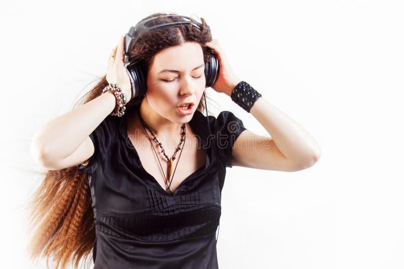 Mujer elegante joven en auriculares grandes que escucha la m?sica y que se divierte fotos de archivo