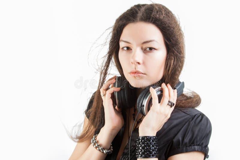 Mujer elegante joven en auriculares grandes que escucha la m?sica y que se divierte imagenes de archivo