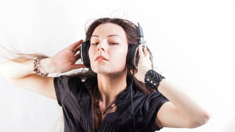 Mujer elegante joven en auriculares grandes que escucha la m?sica y que se divierte imagen de archivo