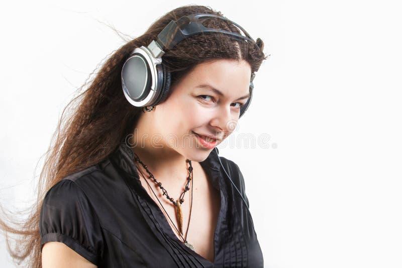 Mujer elegante joven en auriculares grandes que escucha la m?sica y que se divierte fotografía de archivo libre de regalías