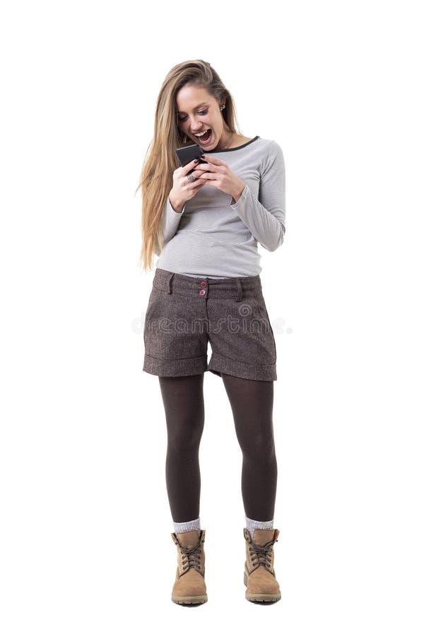 Mujer elegante joven extática que grita mientras que lee y sostiene el teléfono móvil imagen de archivo libre de regalías
