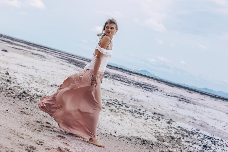Mujer elegante joven hermosa en la playa en la puesta del sol fotos de archivo