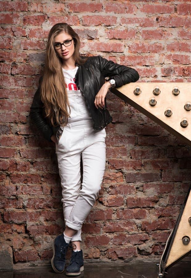 Mujer elegante joven que presenta contra la pared de ladrillo vieja Pantalones blancos y chaqueta de cuero negra imagen de archivo libre de regalías