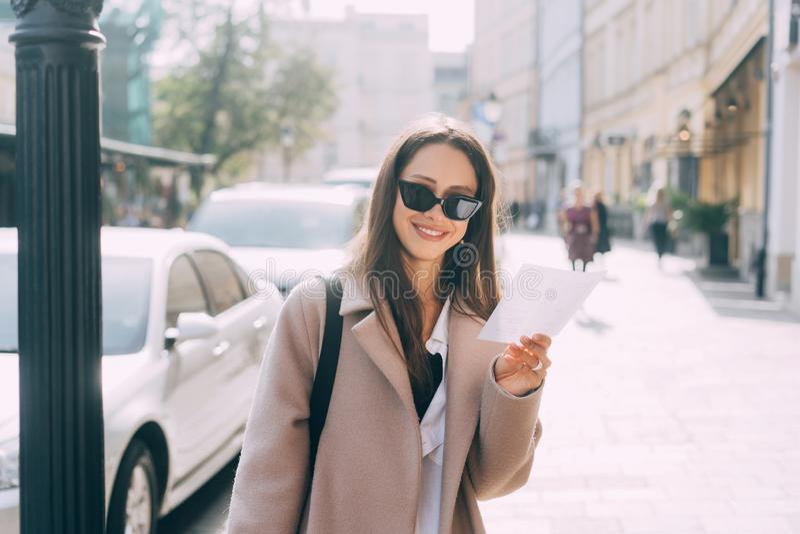Mujer elegante joven que presenta en la calle y que mira la cámara fotografía de archivo
