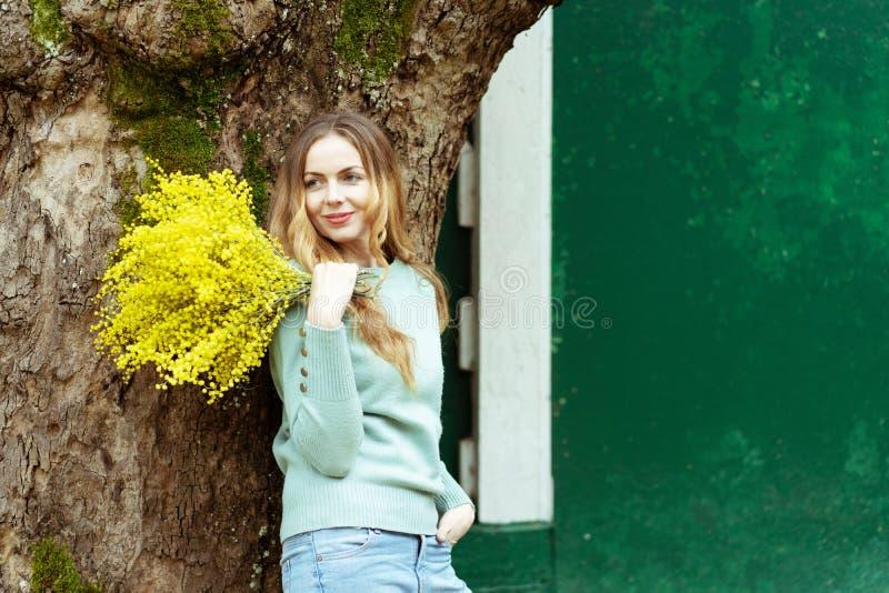 Mujer elegante joven que sonríe sosteniendo un ramo de flores frescas de la mimosa en su mano, el 8 de marzo, el día de madre imágenes de archivo libres de regalías