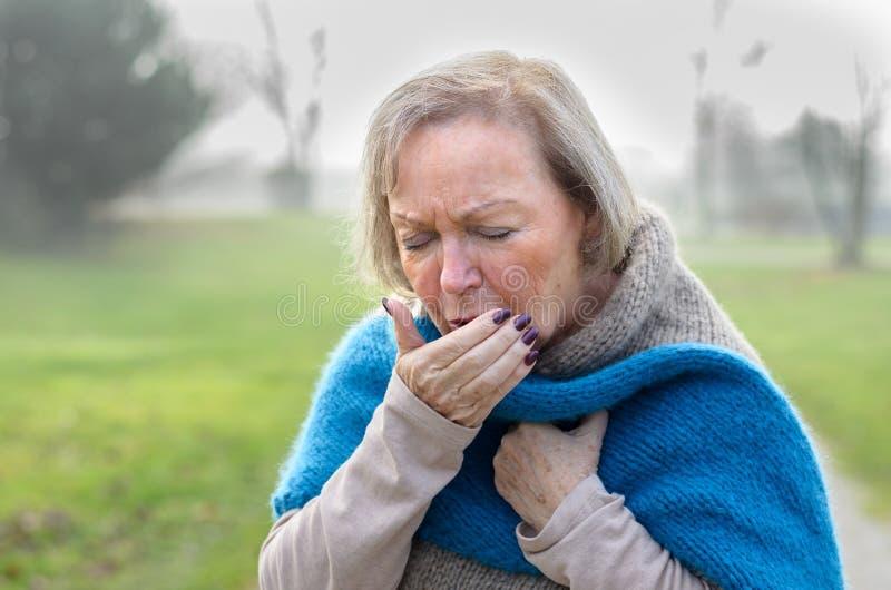 Mujer elegante mayor que tose o que estornuda imágenes de archivo libres de regalías