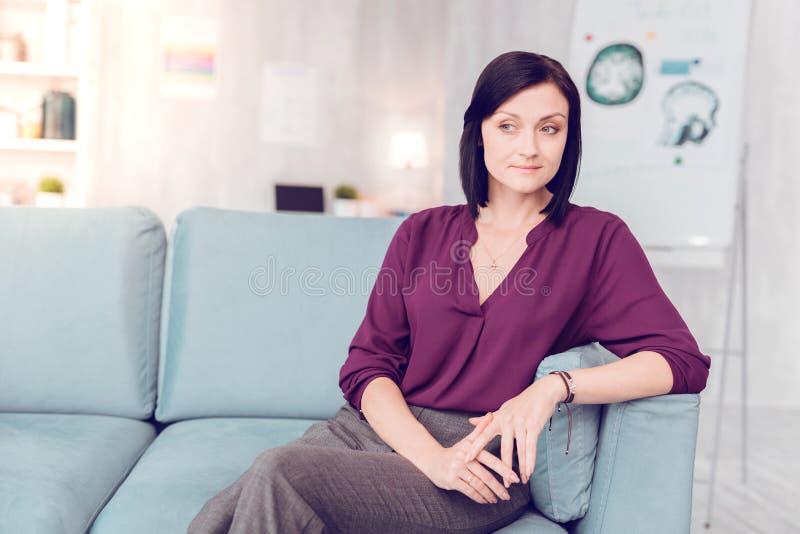 Mujer elegante oscuro-cabelluda hermosa que se sienta en un sofá de la sala de estar imagen de archivo