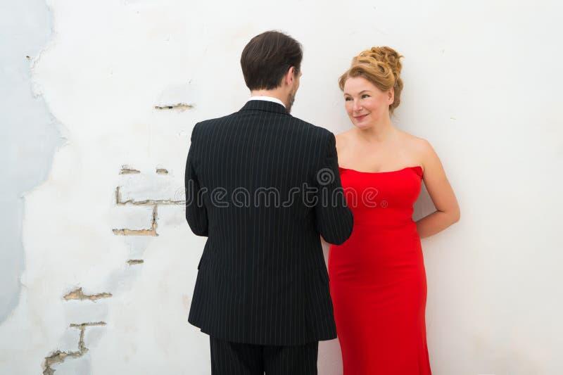 Mujer elegante positiva en vestido rojo que sonríe sinceramente mientras que mira a su marido imagenes de archivo
