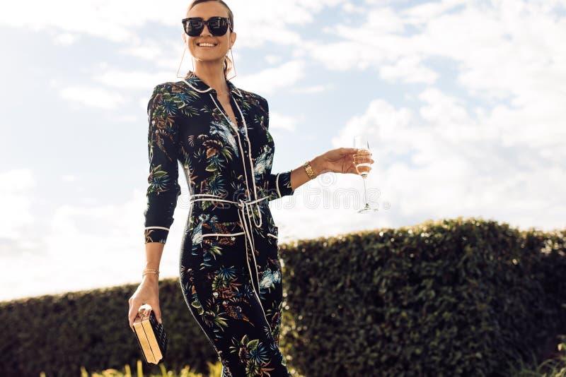 Mujer elegante que camina con el vidrio de vino fotografía de archivo
