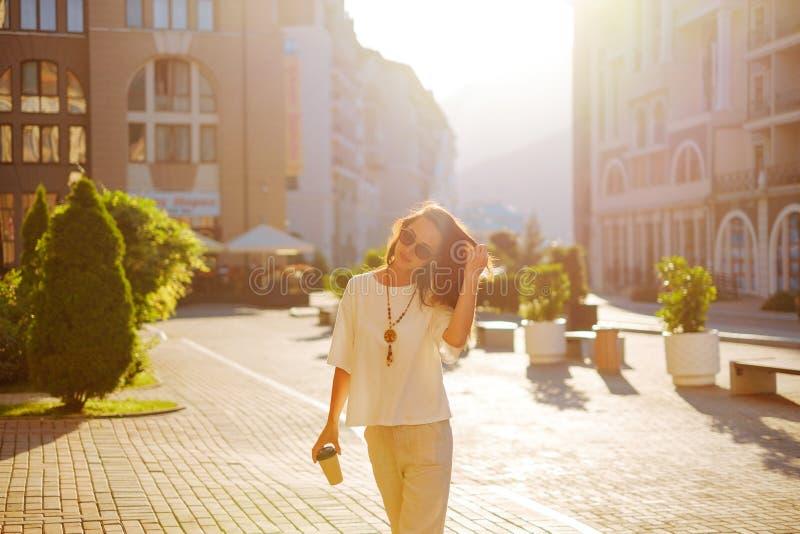 Mujer elegante que camina con la taza de café en calle de la ciudad imágenes de archivo libres de regalías