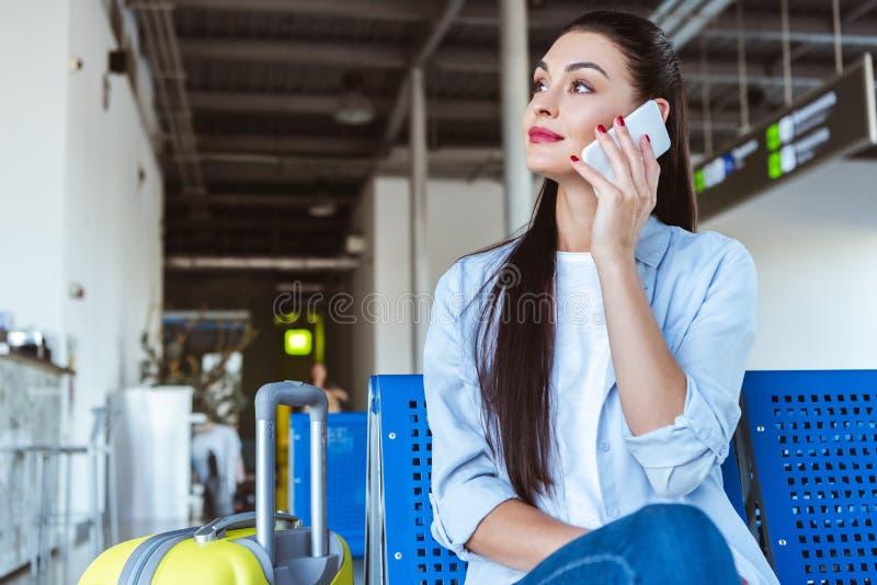 Mujer elegante que habla en smartphone y que se sienta en el aeropuerto fotografía de archivo libre de regalías