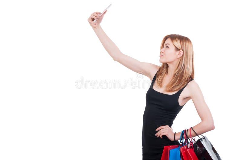 Mujer elegante que hace el selfie con la bolsa de papel fotos de archivo
