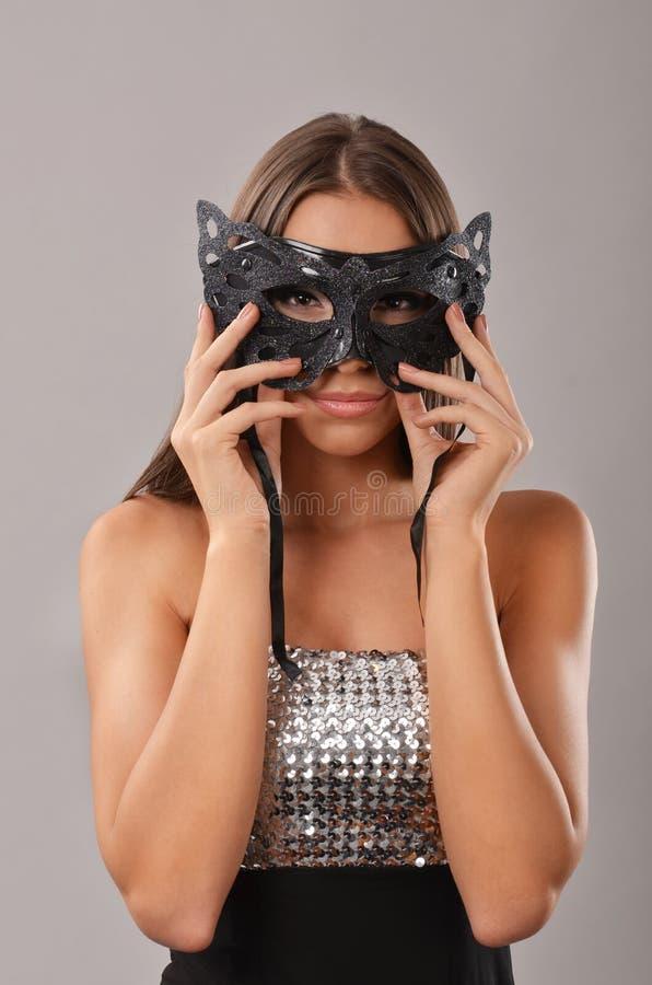Mujer elegante que lleva a cabo una máscara de la mascarada foto de archivo