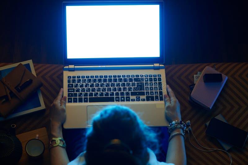 Mujer elegante que mira la pantalla de ordenador ligera azul en el ordenador portátil foto de archivo libre de regalías