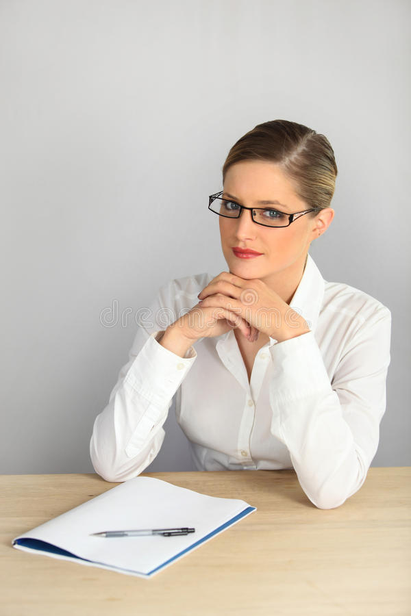 Mujer elegante que se sienta en un escritorio imágenes de archivo libres de regalías