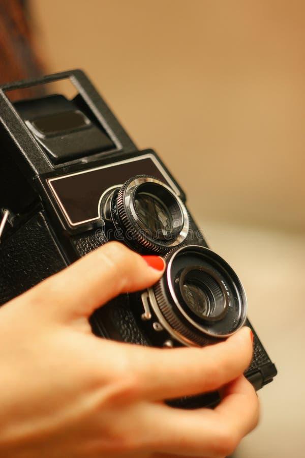 Mujer elegante que se sostiene en cámara análoga de la película de las manos en fondo imagen de archivo libre de regalías