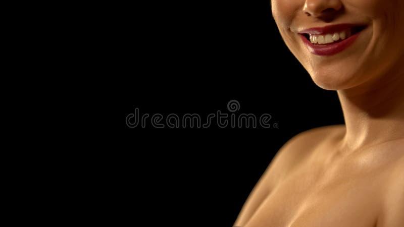 Mujer elegante que sonríe en la cámara, aislada en fondo negro, diente torcido imágenes de archivo libres de regalías