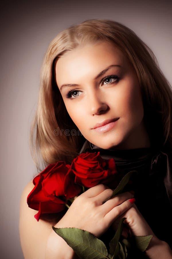 Mujer elegante que sostiene la flor de las rosas imagen de archivo libre de regalías