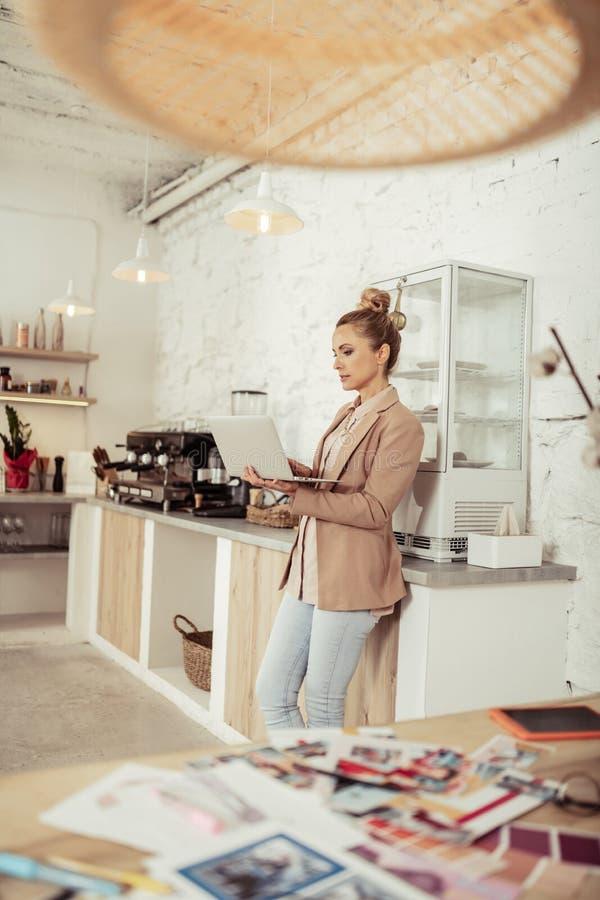 Mujer elegante que trabaja en su ordenador port?til cerca de la m?quina del caf? imágenes de archivo libres de regalías