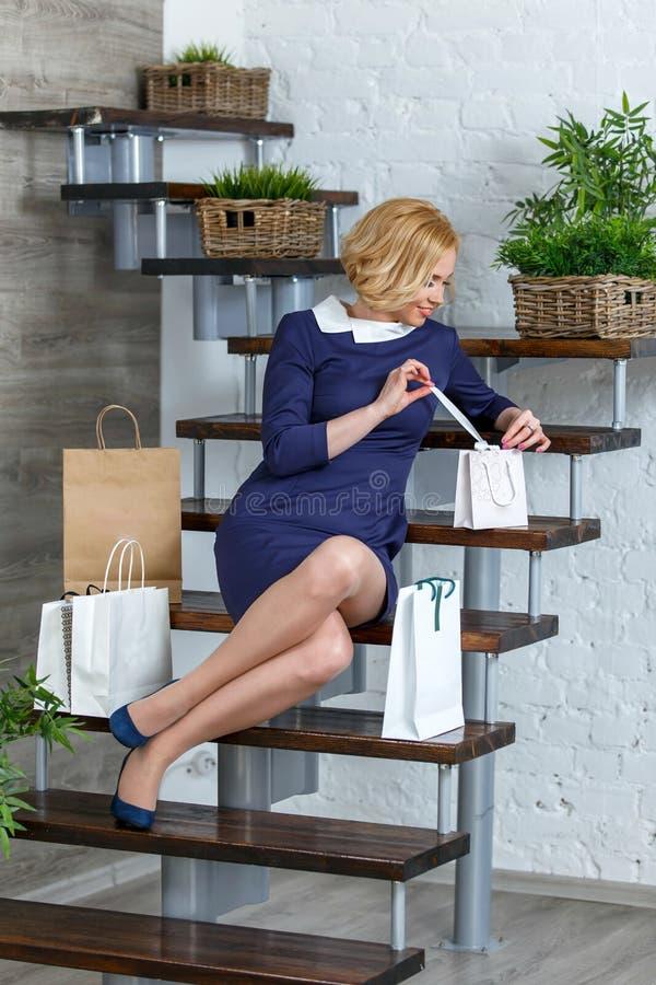 Mujer elegante rubia joven que desempaqueta sus panieres fotografía de archivo libre de regalías