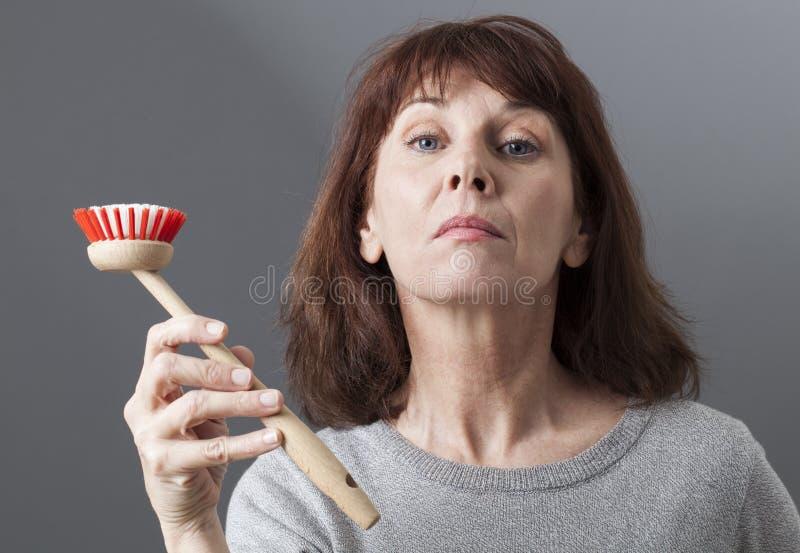 Mujer elegante 50s que entrega el cepillo del plato para lavarse y limpiar en casa imagenes de archivo