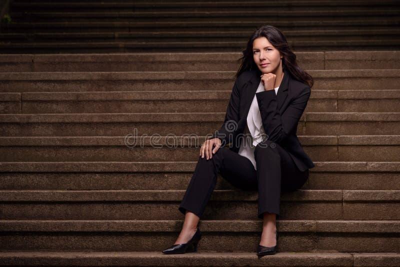 Mujer elegante sonriente que se sienta en pasos fotos de archivo libres de regalías