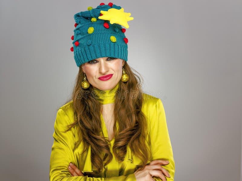 Mujer elegante subrayada en el sombrero divertido de la Navidad aislado en gris imagen de archivo libre de regalías